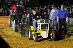 驾驶拖拉机的男孩在拉扯竞争 库存照片