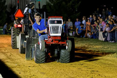 驾驶拖拉机的男孩在拉扯竞争 免版税图库摄影