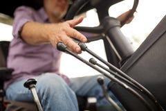 驾驶拖拉机的老人在农场 免版税库存照片