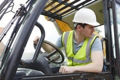 驾驶挖掘者的男性建筑工人 库存照片