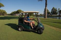 驾驶推车的高尔夫球运动员在路线 免版税库存图片
