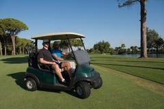 驾驶推车的高尔夫球运动员在路线 免版税库存照片
