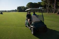 驾驶推车的高尔夫球运动员在路线 图库摄影