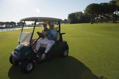 驾驶推车的高尔夫球运动员在路线 库存图片