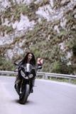 驾驶摩托车的美丽的妇女 免版税库存照片