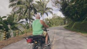 驾驶摩托车的老人在绿色山的弯曲道路盖了旅行热带雨林成人的人  股票录像