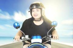 驾驶摩托车的超重妇女 免版税库存照片