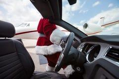 驾驶敞篷车的圣诞老人在机场终端 免版税库存照片