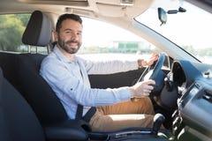 驾驶新的汽车的微笑的人画象在城市 免版税库存图片