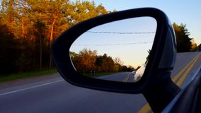 驾驶旁边镜子农村路视图在日落 看在侧视图镜子下的司机观点POV在沿街道的黄昏附近 影视素材