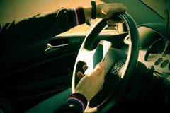 驾驶有一个手机的一个不负责任的人一辆汽车在他的手上 库存图片