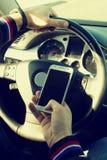 驾驶有一个手机的一个不负责任的人一辆汽车在他的手上 免版税图库摄影