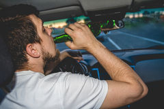 驾驶有一个瓶的一个人一辆汽车啤酒 库存图片