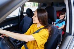 驾驶有儿子的好妇女汽车坐在婴孩位子 免版税图库摄影