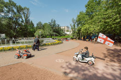 驾驶有全国英王乔治一世至三世时期旗子的未认出的孩子玩具汽车在绿色城市公园 免版税库存照片