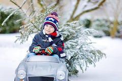 驾驶有圣诞树的滑稽的矮小的微笑的孩子男孩玩具汽车 免版税库存图片