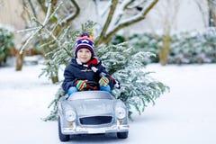驾驶有圣诞树的滑稽的矮小的微笑的孩子男孩玩具汽车 图库摄影