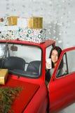 驾驶有圣诞节礼物的妇女一辆汽车 免版税库存照片