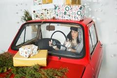 驾驶有圣诞节礼物的妇女一辆汽车 免版税图库摄影