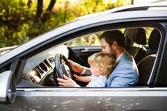 驾驶有小儿子的人一辆汽车 图库摄影