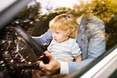 驾驶有小儿子的人一辆汽车 免版税库存图片