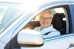 驾驶有开窗口的愉快的老人汽车 库存照片