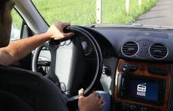 驾驶有收音机的年轻人一辆汽车在机载计算机上 免版税库存照片