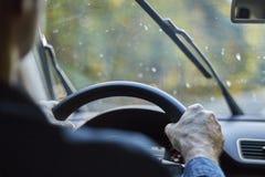 驾驶有移动的风档刮水器的后面观点的一个人一辆汽车在雨期间 库存照片
