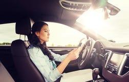 驾驶有smarhphone的妇女汽车 免版税库存照片