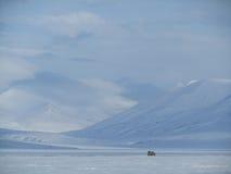驾驶横跨多雪的风景的吉普在斯瓦尔巴特群岛 免版税库存图片