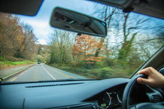 驾驶汽车。在汽车的方向盘的司机的手 库存照片