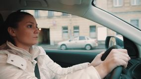 驾驶汽车低谷城市街道的白色夹克的混乱的少妇 股票视频