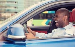 驾驶汽车呼喊的恼怒的被烦死的积极的年轻人 免版税库存照片