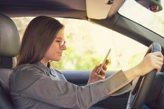 驾驶汽车和使用电话的妇女 免版税图库摄影