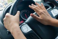 驾驶汽车和按喇叭的妇女 免版税库存照片