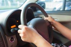 驾驶汽车和控制方向盘的妇女 免版税库存图片