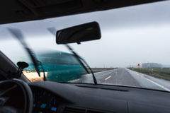 驾驶汽车在恶劣天气情况期间 免版税库存照片