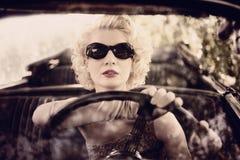 驾驶汽车的减速火箭的妇女 免版税库存图片