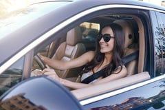 驾驶汽车的妇女佩带的太阳镜 库存图片