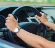 驾驶汽车的妇女的手 免版税库存图片