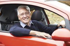 驾驶汽车的微笑的老人画象  免版税图库摄影