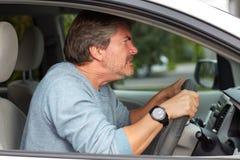 驾驶汽车的恼怒的人 免版税图库摄影