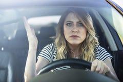 驾驶汽车的恼怒的妇女 免版税图库摄影