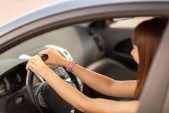 驾驶汽车的愉快的妇女 免版税库存照片