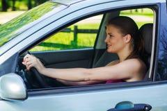 驾驶汽车的愉快的少妇 免版税库存图片