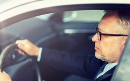 驾驶汽车的愉快的资深商人 库存照片