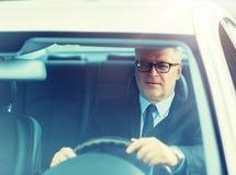 驾驶汽车的愉快的资深商人 免版税库存图片