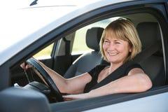 驾驶汽车的成熟妇女 免版税库存照片
