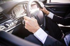 驾驶汽车的男性手 免版税库存照片