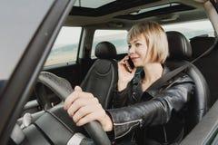 驾驶汽车的皮夹克的企业女孩谈话在电话 免版税库存照片